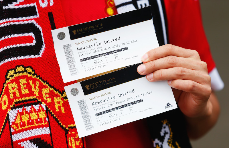 MANCHESTER, ENGLAND - AUGUST 22: A Manchester United fan holds two match tickets prior to the Barclays Premier League match between Manchester United and Newcastle United at Old Trafford on August 22, 2015 in Manchester, England.  (Photo by Julian Finney/Getty Images)