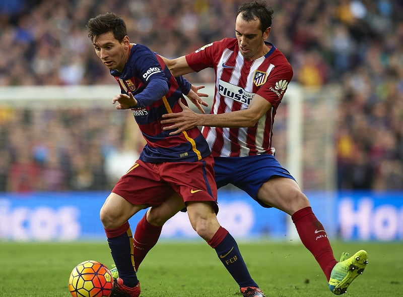 BARCELONA, SPAIN - JANUARY 30:  Lionel Messi (L) of Barcelona is tackled by Godin of Atletico de Madrid during the La Liga match between FC Barcelona and Atletico de Madrid at Camp Nou on January 30, 2016 in Barcelona, Spain.  (Photo by Manuel Queimadelos Alonso/Getty Images)