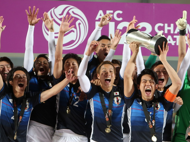 DOHA, QATAR - JANUARY 30:  Japanese footballers celebrate with the trophy after scoring a goal during the AFC U-23 Championship final match between South Korea and Japan at the Abdullah Bin Khalifa Stadium on January 30, 2016 in Doha, Qatar (Photo by Mohamed Farag/Anadolu Agency/Getty Images)