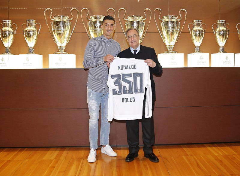 MADRID, SPAIN - MARCH 5: Cristiano Ronaldo (L) of Real Madrid is presented with a shirt to commemorate his 350th goal by Real Madrid President Florentino Perez after the La Liga match between Real Madrid CF and Celta de Vigo at Estadio Santiago Bernabeu on March 5, 2016 in Madrid, Spain. (Photo by Helios de la Rubia/Real Madrid via Getty Images)