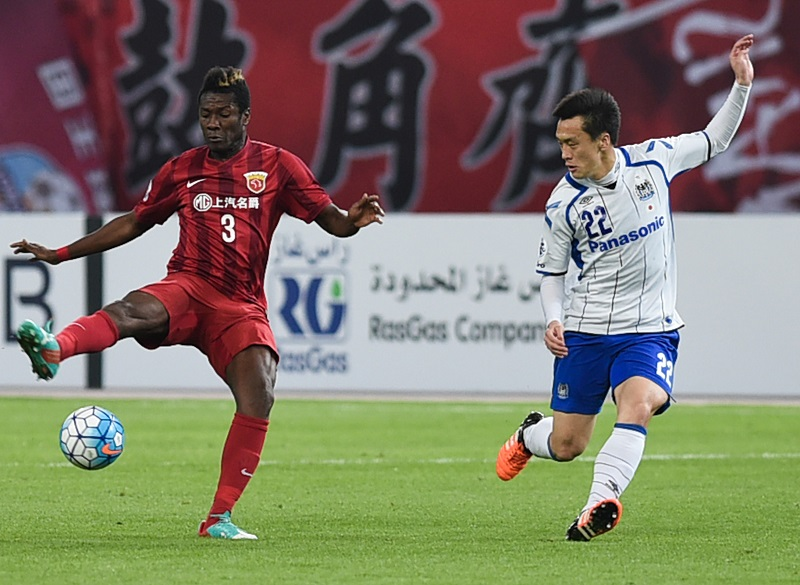 SHANGHAI, CHINA - MARCH 15:  (CHINA OUT) Asamoah Gyan #3 of Shanghai SIPG and Oh Jae-suk #22 of Gamba Osaka compete for the ball during the AFC Champions League Group G match between Shanghai SIPG and Gamba Osaka at Shanghai Stadium on March 15, 2016 in Shanghai, China.  (Photo by ChinaFotoPress/ChinaFotoPress via Getty Images)