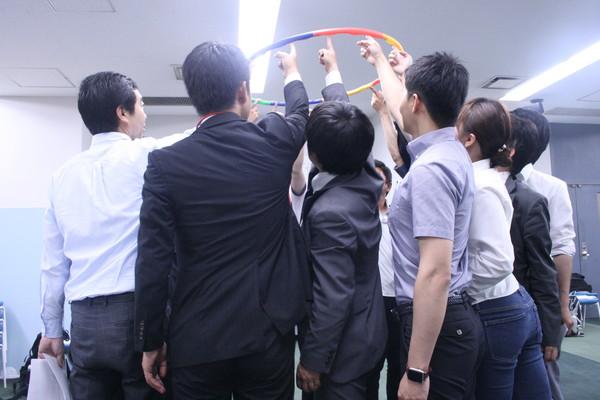グループでフラフープを上から下へと移動させるアクティビティ