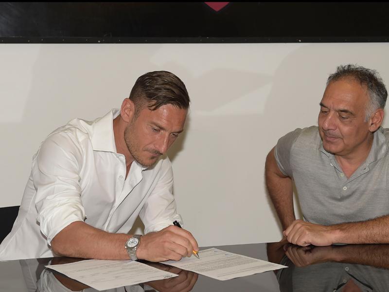パロッタ会長(右)が見守る中で新契約にサイン [写真]=AS Roma via Getty Images