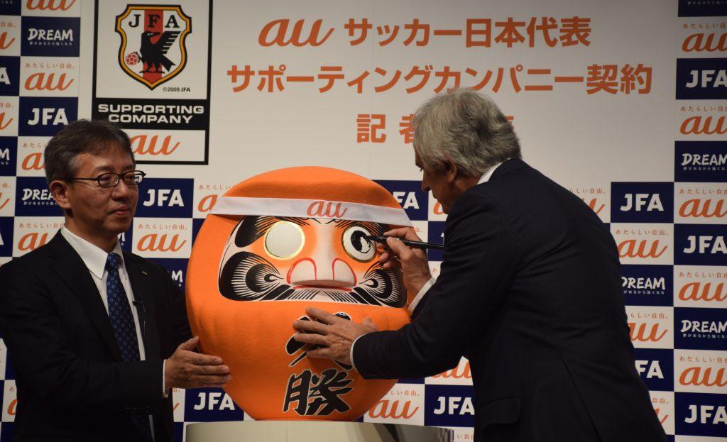 最終予選突破への思いを込めてハリルホジッチ監督はダルマの左目を塗った(左はKDDIの山田隆章コミュニケーション本部長)