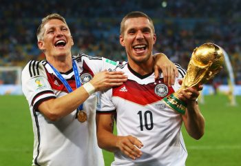RIO DE JANEIRO, BRAZIL - JULY 13:  Bastian Schweinsteiger and Lukas Podolski of Germany celebrate with the World Cup trophy  after defeating Argentina 1-0 in extra time during the 2014 FIFA World Cup Brazil Final match between Germany and Argentina at Maracana on July 13, 2014 in Rio de Janeiro, Brazil.  (Photo by Julian Finney/Getty Images)