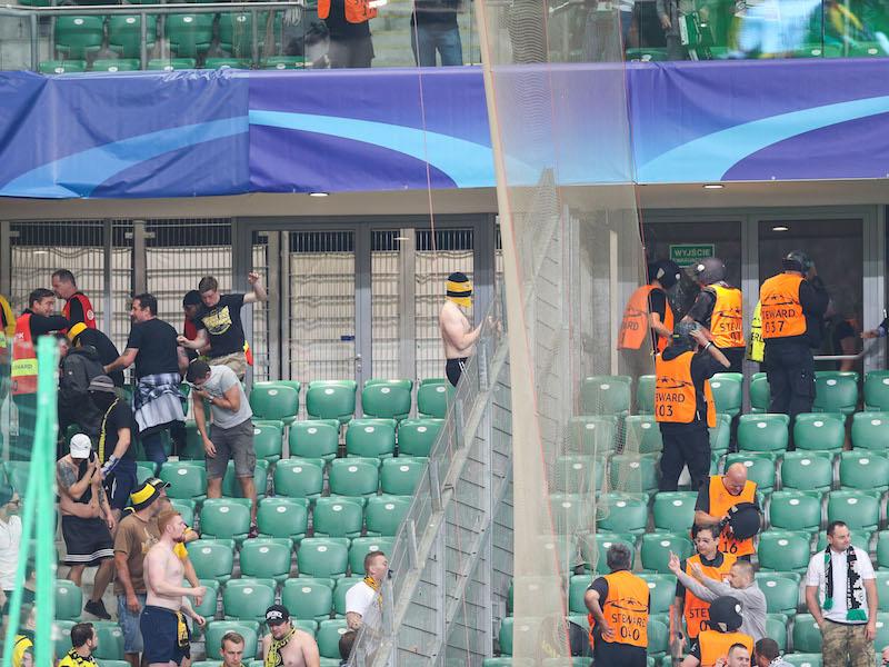 左がドルトムント、右がレギア・ワルシャワ応援席。中指を立てるサポーターも(右下)[写真]=NurPhoto via Getty Images